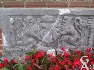 Bas-relief provenant de l'église de La-Haut, construite en 1436 et détruite en 1790, située dans le bois d'Holnon.Vendue en 1790 par adjudication publique avec les autres matériaux de l'église, cette pierre servit très longtemps de pavé à l'entrée d'une maison de ferme d'Holnon. En 1887, elle fut placée au pied du calvaire érigé à l'emplacement de l'église avant que celui-ci ne fut détruit à son tour.Cette pierre funéraire était encastrée dans un mur de l'église en face duquel se trouvait le tombeau d'un homme et d'une femme dont les armoiries s'y voient sculptées. Elles étaient assurément celles d'un seigneur et d'une dame d'Holnon de l'Epée ou d'Attilly qui furent inhumés dans celui-ci.