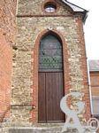 L'église - Porte latérale. On peut lire 1865 sur le mur au dessus du vitrail
